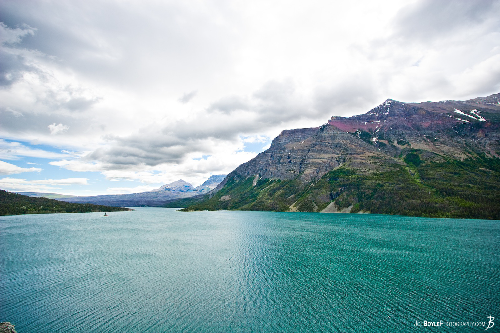 This is one of the first images that I captured on my trip to Glacier National Park (GNP). Beautiful green water, which is a Moraine Lake, with the mountain and clouds as a backdrop provided a very surreal experience!