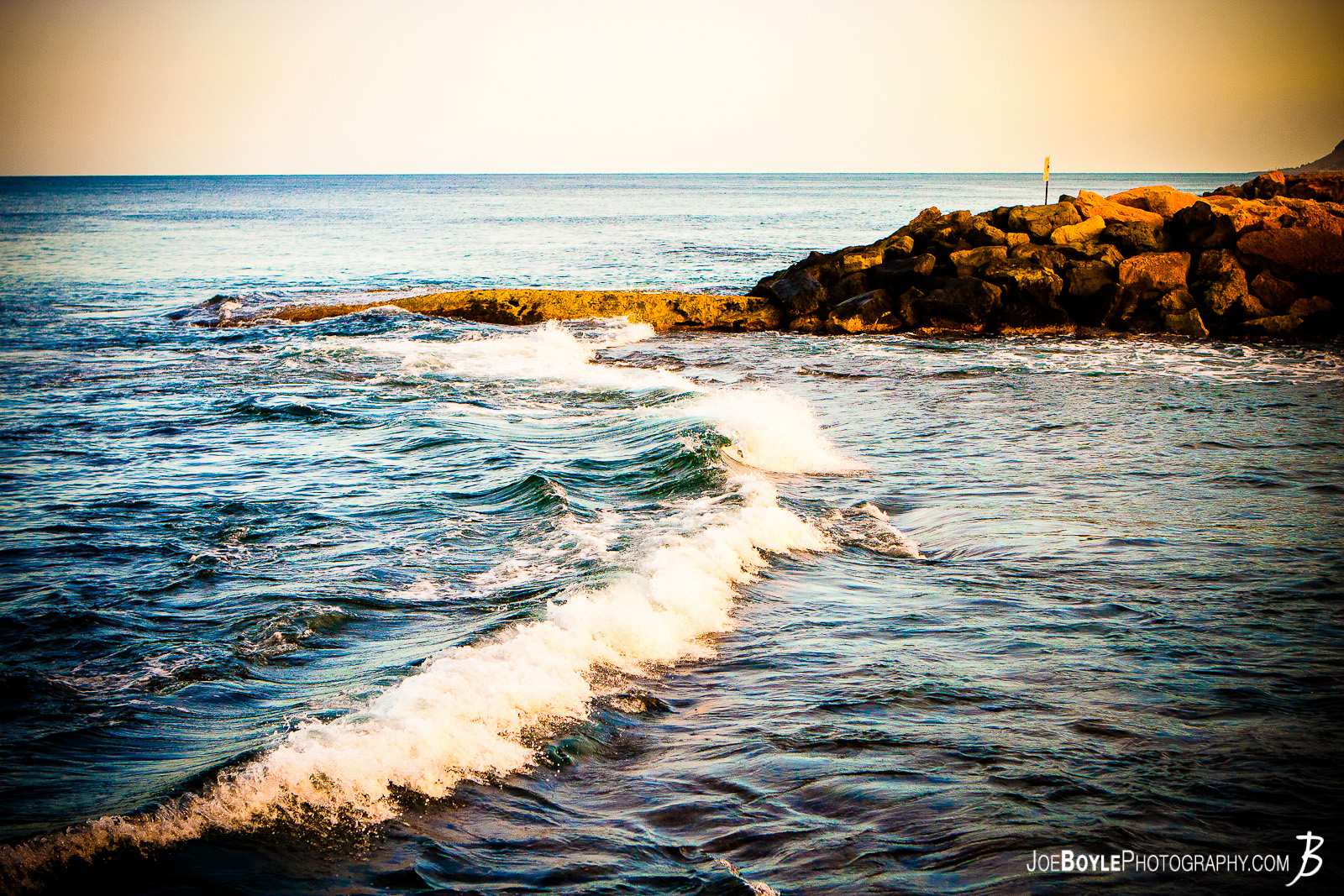 While on a trip to Hawaii I was able to capture this peaceful ocean wave at sunset. It took a few tries to be able to capture it but this is the one I liked the most. I took this near the Disney Aulani Resort on Oahu.