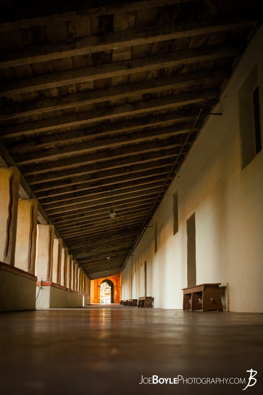 While visiting Carmel by the Sea, my friends and I stopped over at the Carmel Mission Basilica. This is a photo of the hallway at the mission. I really like the repeating wood rafters and long hallway!