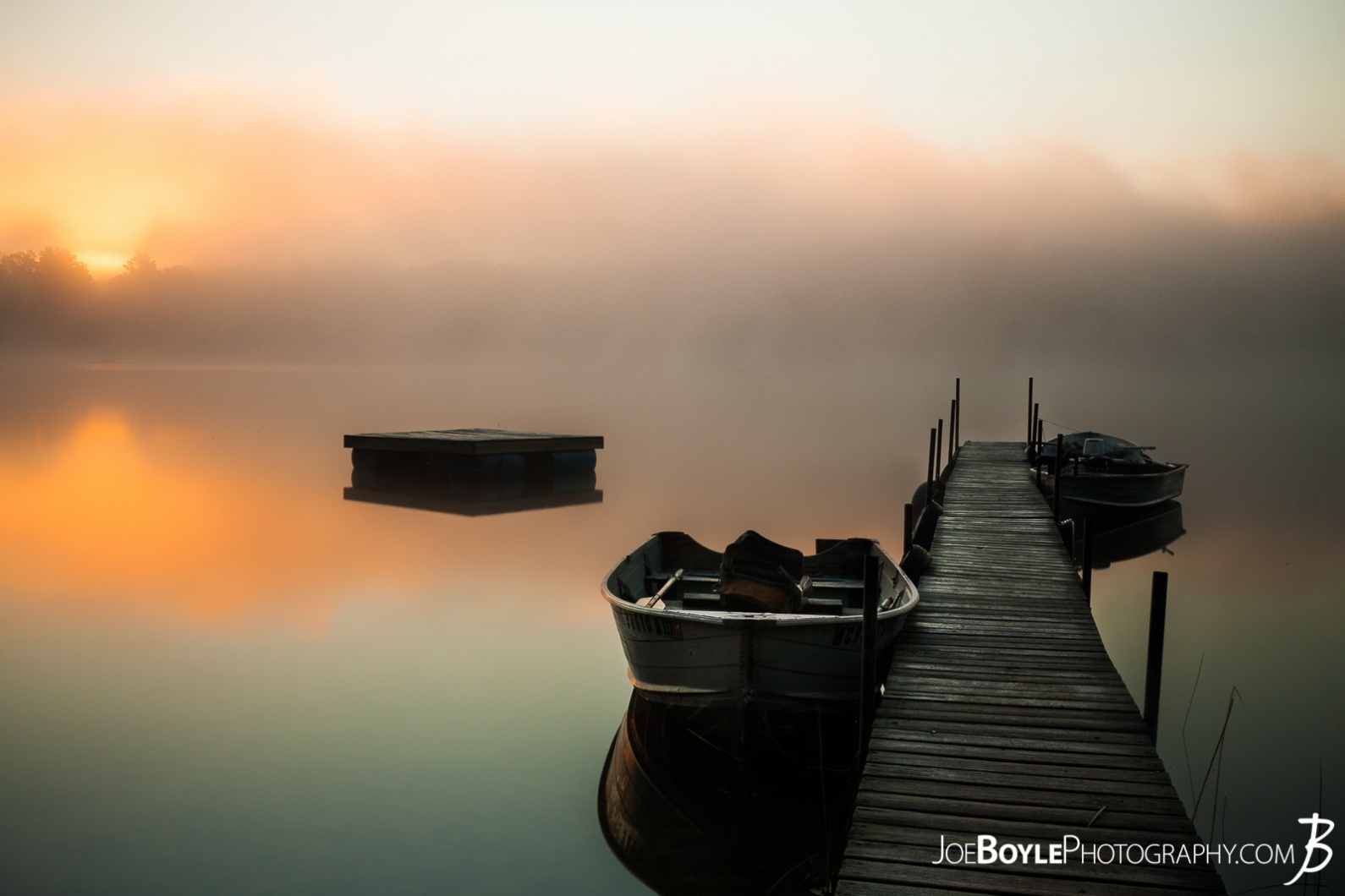 calm-misty-lake-with-pier-and-boats
