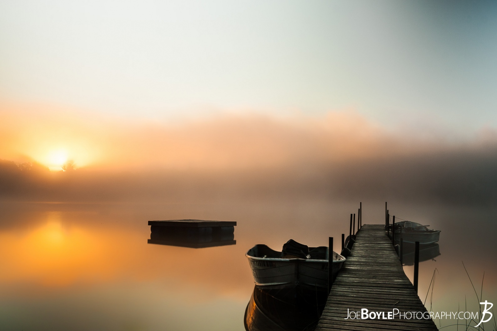 calm-misty-lake-with-pier-and-boats-ii